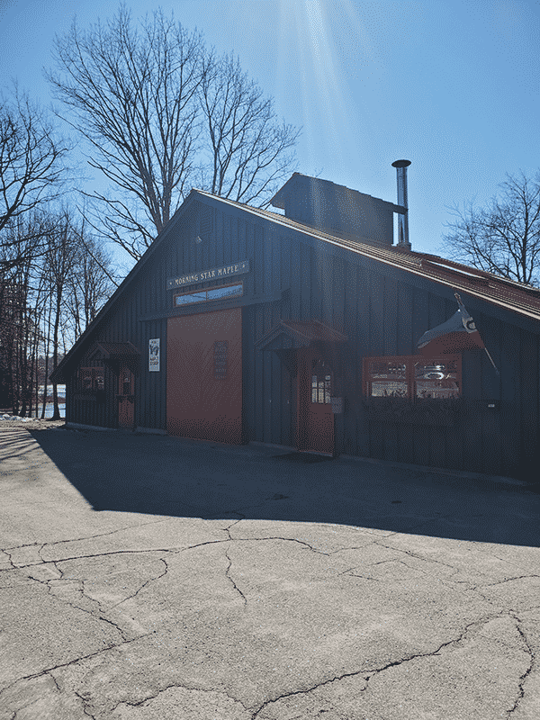 A dark gray building with a red roof sits in the forefront with clear skies in the backdrop. A sign that reads Morning Star Maple hangs on the front