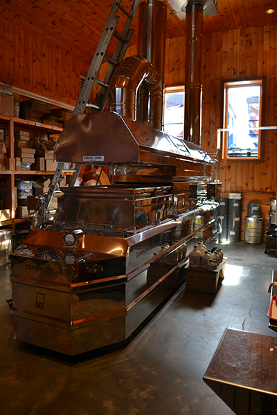 A large metal boiler sits in the center of a barn where it is used to boil down maple sap into syrup