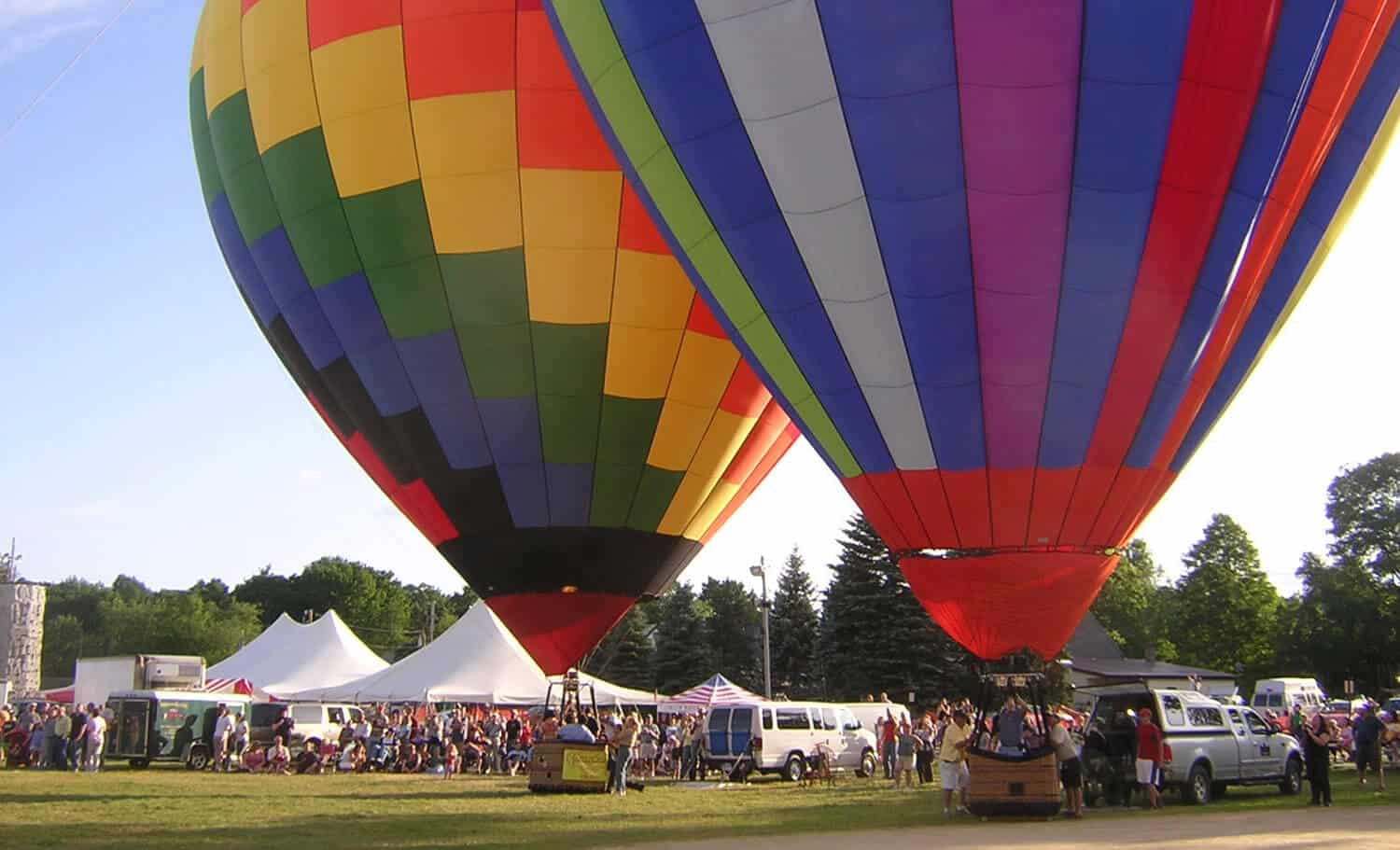 Two hot air balloons await liftoff at a fair