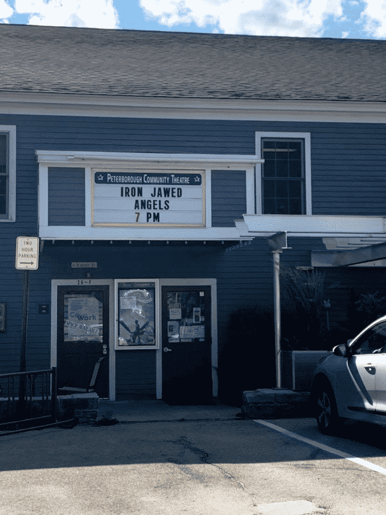 Grey building with a lettered sign for currently playing at the movies.