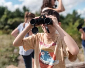 child looking through binoculars outside with others