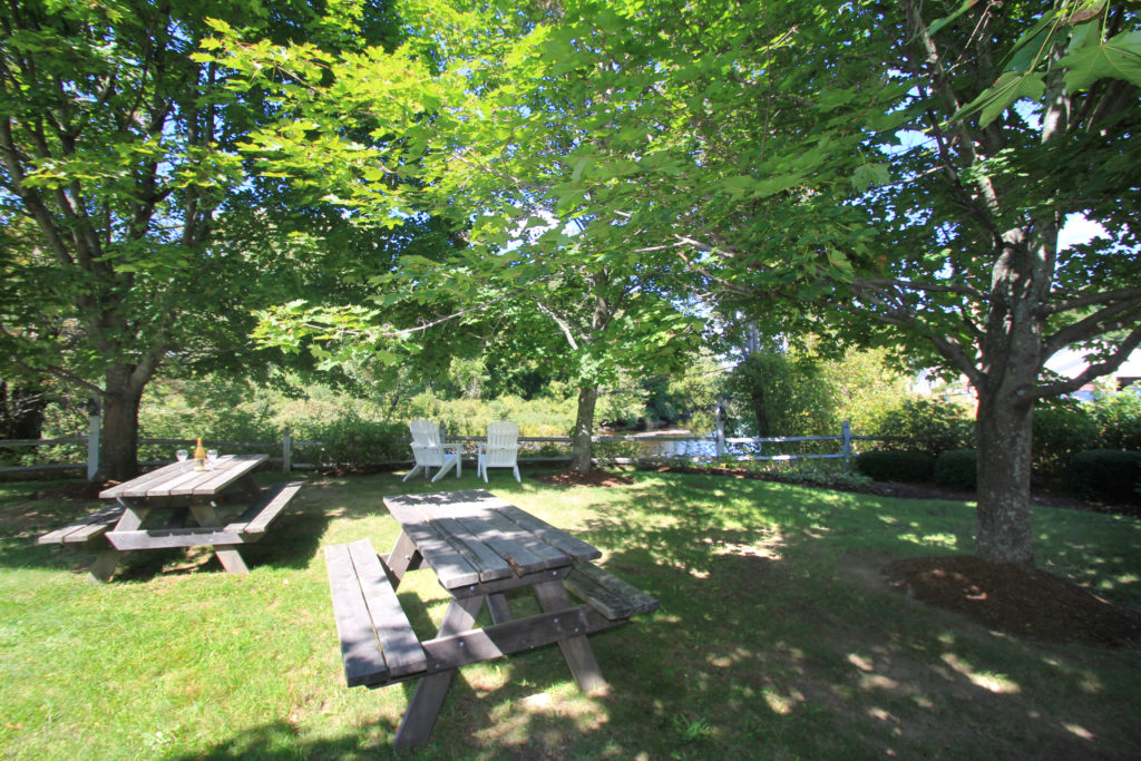 Two picnic tables sit near each other while two white adirondack chairs face the river. A metal fenc separates the grassy area from the river.