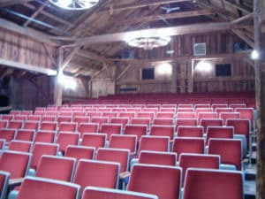 Rows of theater seats in a well lit barn playhouse.