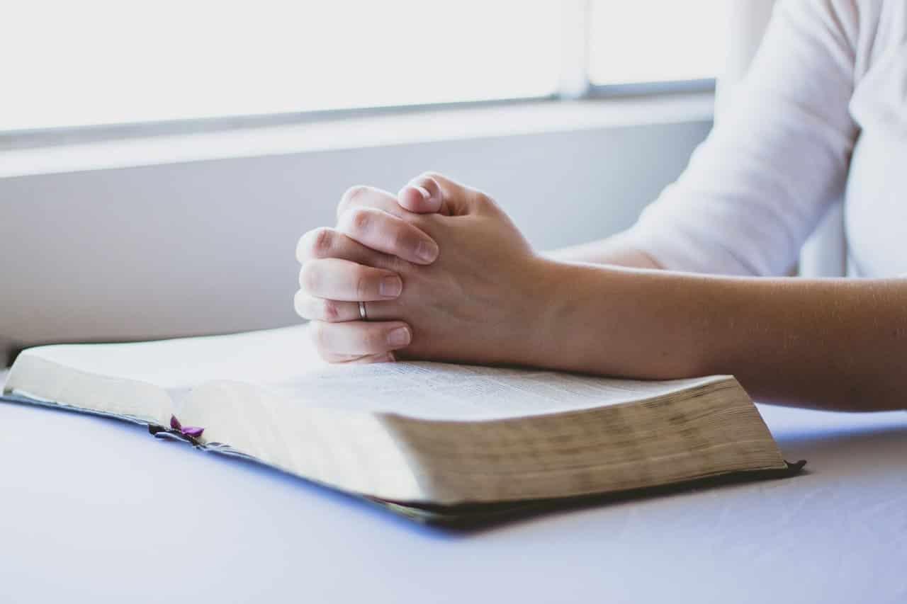 hands folded together over a bible