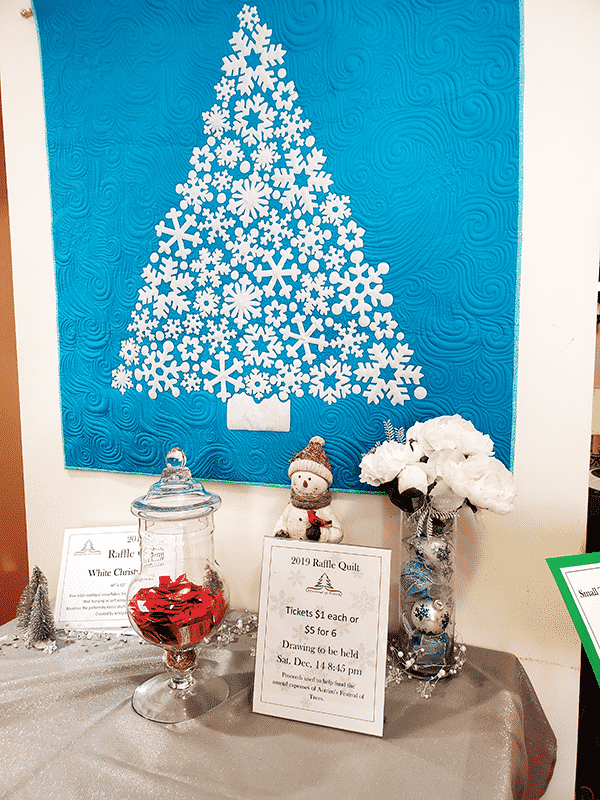A quilted christmas tree made out of white snowflakes on a blue background