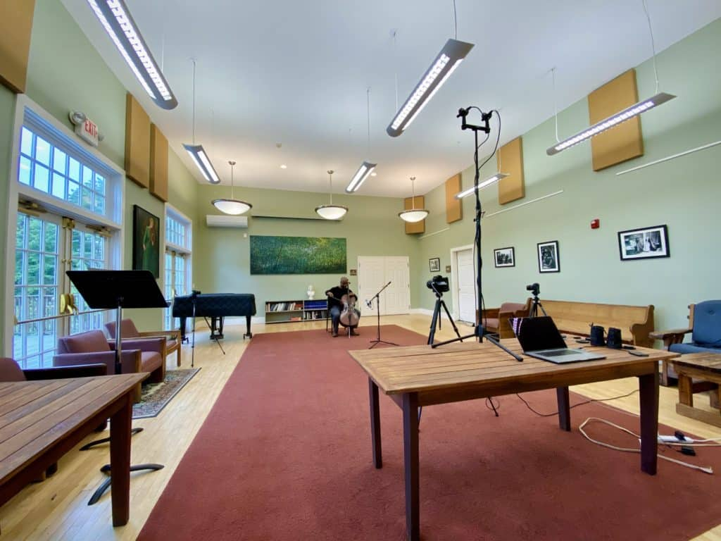 A room with recording devices focus on a musician playing a cello.