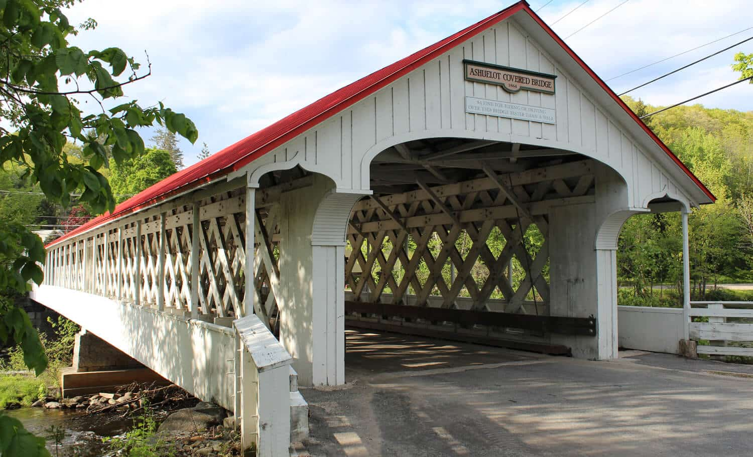 A white and red covered bridge connects the road over a river