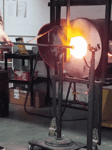 a large furnace for glassblowing heats up molten glass on the end of a metal pipe.
