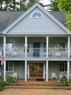 Red brick entry walkway contrasts with the gray-stained exterior of the two storied inn.