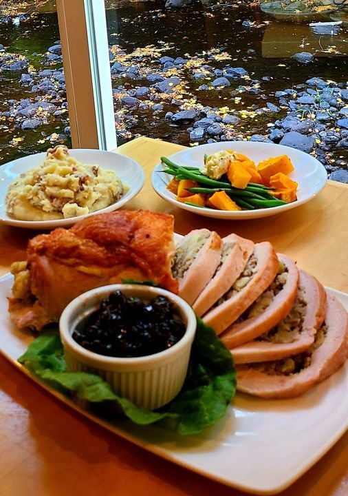 Spread of stuffed turkey breast, cranberry sauce, sauteed veggies and mashed potatoes on a table overlooking the river at Waterhouse Restaurant