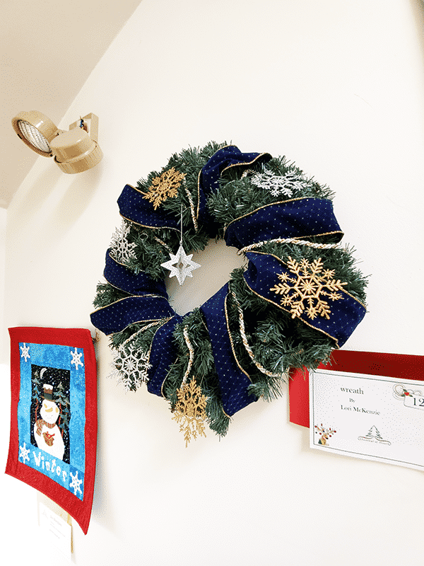 A wreath decorated with blue ribbon and gold snowflakes