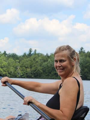 A kayaker glance over her shoulder and paddles across a lake framed by trees and a gray-topped mountain