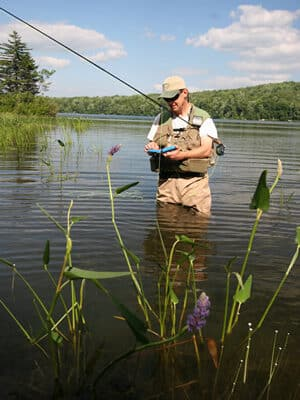 A fly fisherman wearing light brown waders stands in hip deep water as he examines his fly box.